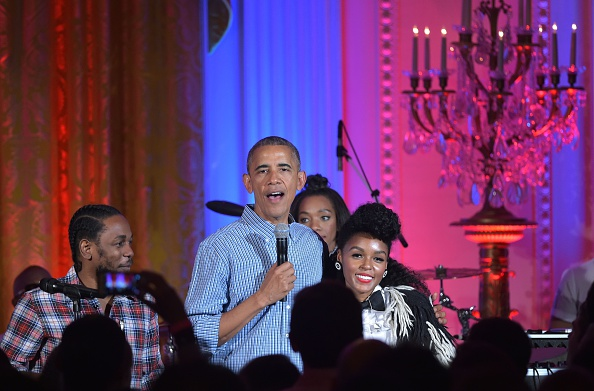 US President Barack Obama (C) stands with performers Kendrick Lamar (L) and Janelle Monáe (R) and speaks during an Independence Day Celebration for military members and administration staff on July 4, 2016 in the East Room of the White House in Washington, DC. / AFP / Mandel NGAN (Photo credit should read MANDEL NGAN/AFP/Getty Images)