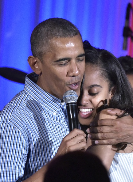 US President Barack Obama hugs his daughter Malia on her birthday during an Independence Day Celebration for military members and administration staff on July 4, 2016 in the East Room of the White House in Washington, DC. / AFP / Mandel Ngan (Photo credit should read MANDEL NGAN/AFP/Getty Images)
