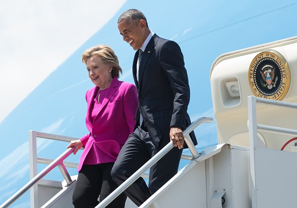US President Barack Obama and Democratic presidential candidate Hillary Clinton walk off Air Force One in Charlotte, North Carolina, to attend a Clinton campaign event. / AFP / NICHOLAS KAMM (Photo credit should read NICHOLAS KAMM/AFP/Getty Images)