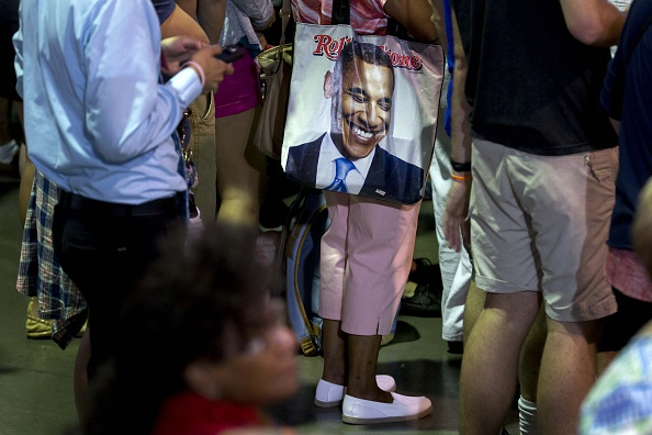 An attendee carries a tote bag with the caricature of U.S. President Barack Obama during a campaign rally for Hillary Clinton, presumptive 2016 Democratic presidential nominee, not pictured, the Charlotte Convention Center in Charlotte, North Carolina, U.S., on Tuesday, July 5, 2016. Clintons path to the White House relies on reassembling the winning Obama coalition of minority voters and women, but her campaign is vying for a demographic long out of reach for Democrats -- college-educated whites -- that could reshape the map of U.S. swing states this year. Photographer: Andrew Harrer/Bloomberg via Getty Images
