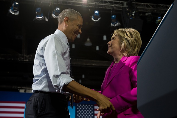 """US President Barack Obama and Democratic presidential candidate Hillary Clinton take part in a campaign event in Charlotte, North Carolina, on July 5, 2016. US President Barack Obama threw his full weight behind Hillary Clinton's bid to succeed him, extolling the experience and fighting spirit of his former secretary of state at their first joint campaign appearance. """"I'm here today because I believe in Hillary Clinton,"""" Obama told the rally in Charlotte, North Carolina. """"There has never been any man or woman more qualified for this office."""" / AFP / NICHOLAS KAMM (Photo credit should read NICHOLAS KAMM/AFP/Getty Images)"""
