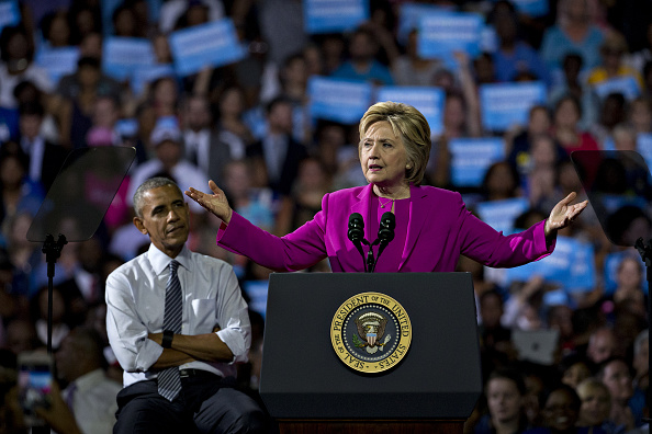 Hillary Clinton, presumptive 2016 Democratic presidential nominee, speaks as U.S. President Barack Obama, left, listens during a campaign rally at the Charlotte Convention Center in Charlotte, North Carolina, U.S., on Tuesday, July 5, 2016. Obama, making his debut campaign appearance on Clinton's behalf, flew with her on Air Force One as a show of unity and power hours after the FBI director called Clinton's handling of sensitive e-mails as Secretary of State extremely careless. Photographer: Andrew Harrer/Bloomberg via Getty Images