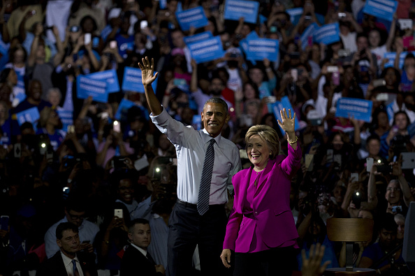 U.S. President Barack Obama, left, and Hillary Clinton, presumptive 2016 Democratic presidential nominee, wave while walking out to speak during a campaign rally at the Charlotte Convention Center in Charlotte, North Carolina, U.S., on Tuesday, July 5, 2016. Obama, making his debut campaign appearance on Clinton's behalf, flew with her on Air Force One as a show of unity and power hours after the FBI director called Clinton's handling of sensitive e-mails as Secretary of State extremely careless. Photographer: Andrew Harrer/Bloomberg via Getty Images