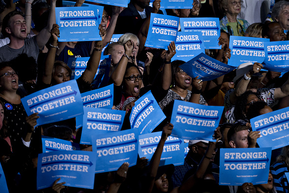 Attendees hold campaign signs as U.S. President Barack Obama, not pictured, speaks during a campaign rally with Hillary Clinton, presumptive 2016 Democratic presidential nominee, not pictured, at the Charlotte Convention Center in Charlotte, North Carolina, U.S., on Tuesday, July 5, 2016. Obama, making his debut campaign appearance on Clinton's behalf, flew with her on Air Force One as a show of unity and power hours after the FBI director called Clinton's handling of sensitive e-mails as Secretary of State extremely careless. Photographer: Andrew Harrer/Bloomberg via Getty Images
