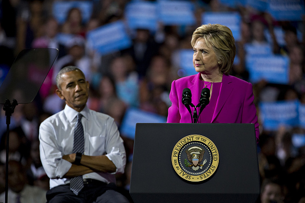 Hillary Clinton, presumptive 2016 Democratic presidential nominee, pauses while speaking as U.S. President Barack Obama, left, listens during a campaign rally at the Charlotte Convention Center in Charlotte, North Carolina, U.S., on Tuesday, July 5, 2016. Obama, making his debut campaign appearance on Clinton's behalf, flew with her on Air Force One as a show of unity and power hours after the FBI director called Clinton's handling of sensitive e-mails as Secretary of State extremely careless. Photographer: Andrew Harrer/Bloomberg via Getty Images