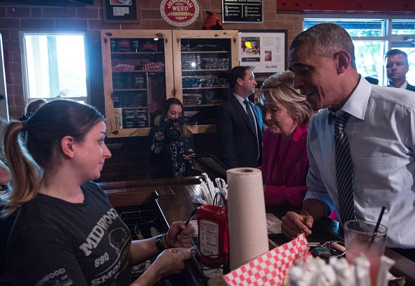 """US President Barack Obama and Democratic presidential candidate Hillary Clinton order food at Midwood Smokehouse in Charlotte, North Carolina, on July 5, 2016. US President Barack Obama threw his full weight behind Hillary Clinton's bid to succeed him, extolling the experience and fighting spirit of his former secretary of state at their first joint campaign appearance. """"I'm here today because I believe in Hillary Clinton,"""" Obama told the rally in Charlotte, North Carolina. """"There has never been any man or woman more qualified for this office."""" / AFP / NICHOLAS KAMM (Photo credit should read NICHOLAS KAMM/AFP/Getty Images)"""