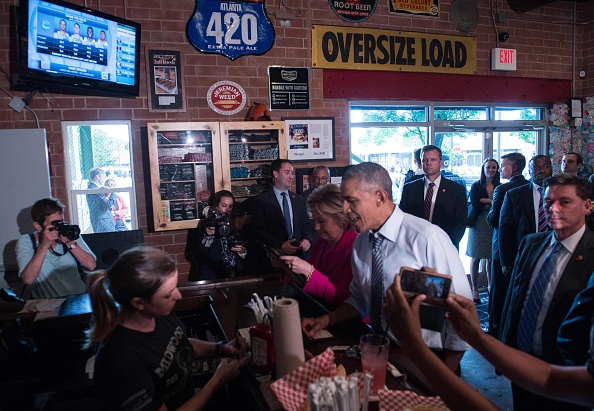 "US President Barack Obama and Democratic presidential candidate Hillary Clinton order food at Midwood Smokehouse in Charlotte, North Carolina, on July 5, 2016. US President Barack Obama threw his full weight behind Hillary Clinton's bid to succeed him, extolling the experience and fighting spirit of his former secretary of state at their first joint campaign appearance. ""I'm here today because I believe in Hillary Clinton,"" Obama told the rally in Charlotte, North Carolina. ""There has never been any man or woman more qualified for this office."" / AFP / NICHOLAS KAMM (Photo credit should read NICHOLAS KAMM/AFP/Getty Images)"