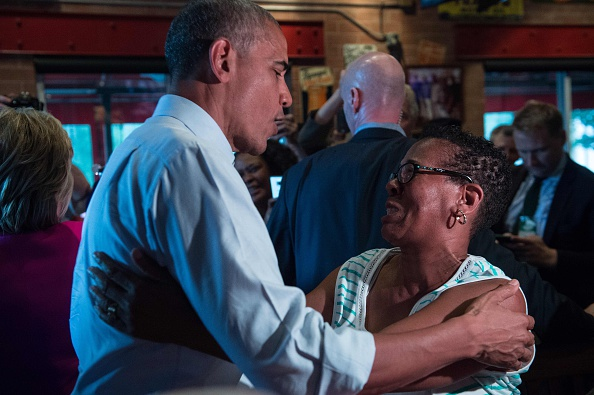 "US President Barack Obama greets a patron at Midwood Smokehouse in Charlotte, North Carolina, on July 5, 2016. US President Barack Obama threw his full weight behind Hillary Clinton's bid to succeed him, extolling the experience and fighting spirit of his former secretary of state at their first joint campaign appearance. ""I'm here today because I believe in Hillary Clinton,"" Obama told the rally in Charlotte, North Carolina. ""There has never been any man or woman more qualified for this office."" / AFP / NICHOLAS KAMM (Photo credit should read NICHOLAS KAMM/AFP/Getty Images)"