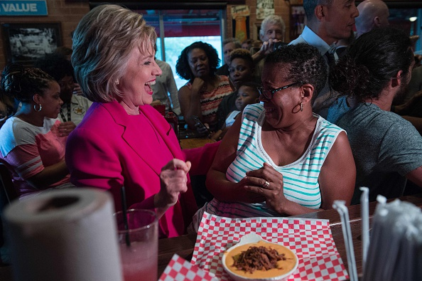 "US Democratic presidential candidate Hillary Clinton greets a patron at Midwood Smokehouse in Charlotte, North Carolina, on July 5, 2016. US President Barack Obama threw his full weight behind Hillary Clinton's bid to succeed him, extolling the experience and fighting spirit of his former secretary of state at their first joint campaign appearance. ""I'm here today because I believe in Hillary Clinton,"" Obama told the rally in Charlotte, North Carolina. ""There has never been any man or woman more qualified for this office."" / AFP / NICHOLAS KAMM (Photo credit should read NICHOLAS KAMM/AFP/Getty Images)"