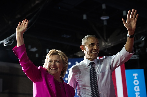"""US President Barack Obama and Democratic presidential candidate Hillary Clinton leave a campaign event in Charlotte, North Carolina, on July 5, 2016. US President Barack Obama threw his full weight behind Hillary Clinton's bid to succeed him, extolling the experience and fighting spirit of his former secretary of state at their first joint campaign appearance. """"I'm here today because I believe in Hillary Clinton,"""" Obama told the rally in Charlotte, North Carolina. """"There has never been any man or woman more qualified for this office."""" / AFP / NICHOLAS KAMM (Photo credit should read NICHOLAS KAMM/AFP/Getty Images)"""