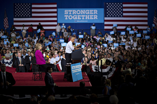 U.S. President Barack Obama speaks as Hillary Clinton, presumptive 2016 Democratic presidential nominee, left, listens during a campaign rally at the Charlotte Convention Center in Charlotte, North Carolina, U.S., on Tuesday, July 5, 2016. Obama, making his debut campaign appearance on Clinton's behalf, flew with her on Air Force One as a show of unity and power hours after the FBI director called Clinton's handling of sensitive e-mails as Secretary of State extremely careless. Photographer: Andrew Harrer/Bloomberg via Getty Images