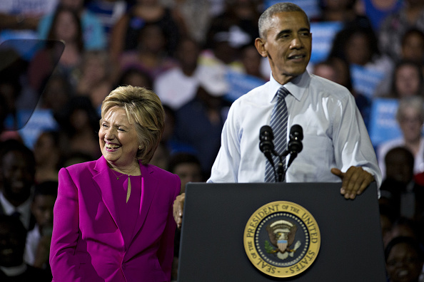 Hillary Clinton, presumptive 2016 Democratic presidential nominee, left, smiles as U.S. President Barack Obama speaks during a campaign rally at the Charlotte Convention Center in Charlotte, North Carolina, U.S., on Tuesday, July 5, 2016. Obama, making his debut campaign appearance on Clinton's behalf, flew with her on Air Force One as a show of unity and power hours after the FBI director called Clinton's handling of sensitive e-mails as Secretary of State extremely careless. Photographer: Andrew Harrer/Bloomberg via Getty Images