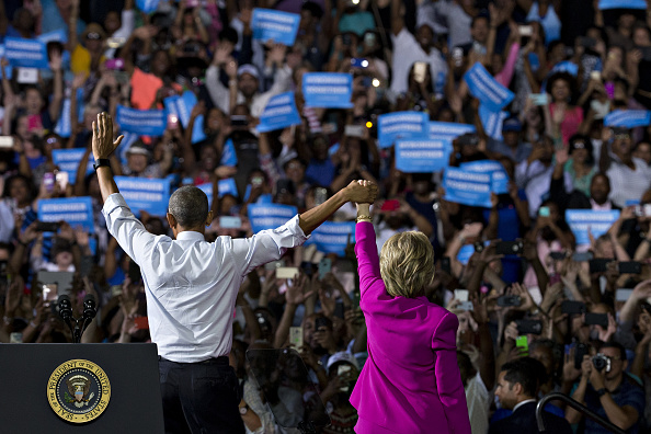 Hillary Clinton, presumptive 2016 Democratic presidential nominee, right, and U.S. President Barack Obama raise their hands after speaking during a campaign rally at the Charlotte Convention Center in Charlotte, North Carolina, U.S., on Tuesday, July 5, 2016. Obama, making his debut campaign appearance on Clinton's behalf, flew with her on Air Force One as a show of unity and power hours after the FBI director called Clinton's handling of sensitive e-mails as Secretary of State extremely careless. Photographer: Andrew Harrer/Bloomberg via Getty Images