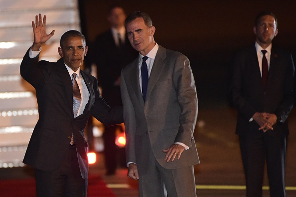 US President Barack Obama (L) waves beside Spain's King Felipe VI on arrival at the Torrejon airbase near Madrid on July 9, 2016. Barack Obama began a shortened but symbolic first presidential trip to Spain Saturday, squeezing in a visit to a key ally before dashing home to deal with the aftermath of wrenching shooting in Dallas / AFP / PIERRE-PHILIPPE MARCOU (Photo credit should read PIERRE-PHILIPPE MARCOU/AFP/Getty Images)