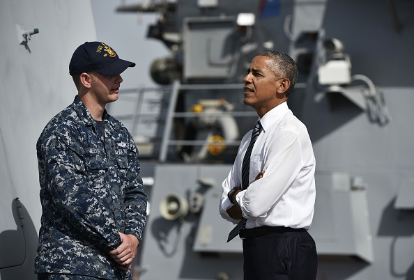 US President Barack Obama (R) chats with a soldier as he tours the USS Ross Navy ship at the Naval Station Rota, in Rota, southwestern Spain on July 10, 2016. Obama said he will cut short a foreign trip and visit Dallas next week as the shooting rampage by the black army veteran, who said he wanted to kill white cops, triggered urgent calls to mend troubled race relations in the United States. / AFP / Mandel Ngan (Photo credit should read MANDEL NGAN/AFP/Getty Images)