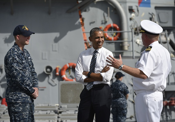 US President Barack Obama (C) listens to a commander as he tours the USS Ross Navy ship at the Naval Station Rota, in Rota, southwestern Spain on July 10, 2016. Obama said he will cut short a foreign trip and visit Dallas next week as the shooting rampage by the black army veteran, who said he wanted to kill white cops, triggered urgent calls to mend troubled race relations in the United States. / AFP / MANDEL NGAN (Photo credit should read MANDEL NGAN/AFP/Getty Images)