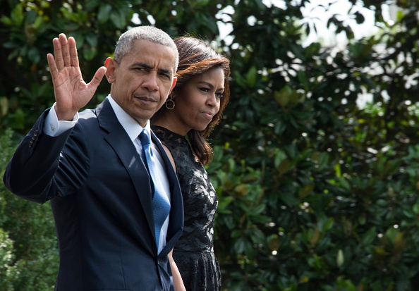 US President Barack Obama and First Lady Michelle Obama walk to board Marine One on July 12, 2016 at the White House in Washington, DC, before departing for Dallas following the killing of five policemen by a sniper. / AFP / NICHOLAS KAMM (Photo credit should read NICHOLAS KAMM/AFP/Getty Images)