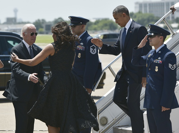 US Vice President Joe Biden (L), receives a hug from First Lady Michelle Obama as US President Barack Obama steps off Air Force One upon arrival at Dallas Love Field in Dallas, Texas on July 12, 2016. / AFP / MANDEL NGAN (Photo credit should read MANDEL NGAN/AFP/Getty Images)