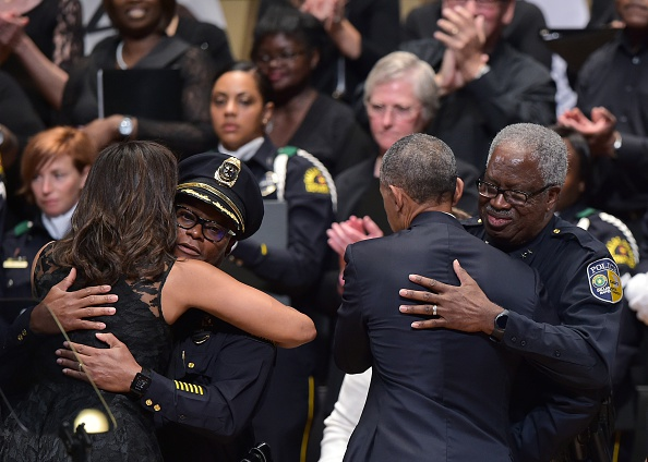 First Lady Michelle Obama hugs Dallas Police Chief David Brown (2nd L) as US President Barack Obama hugs Dallas Area Rapid Transit Police Chief James Spiller (R) during an interfaith memorial service for the victims of the Dallas police shooting at the Morton H. Meyerson Symphony Center on July 12, 2016 in Dallas, Texas. President Barack Obama attended a somber memorial Tuesday to five police officers slain in a sniper ambush in Dallas, as he seeks to unify a country divided by race and politics. / AFP / MANDEL NGAN (Photo credit should read MANDEL NGAN/AFP/Getty Images)