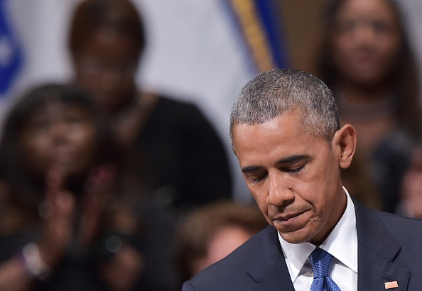 US President Barack Obama pauses speaks during an interfaith memorial service for the victims of the Dallas police shooting at the Morton H. Meyerson Symphony Center on July 12, 2016 in Dallas, Texas. President Barack Obama attended a somber memorial Tuesday to five police officers slain in a sniper ambush in Dallas, as he seeks to unify a country divided by race and politics. / AFP / MANDEL NGAN (Photo credit should read MANDEL NGAN/AFP/Getty Images)