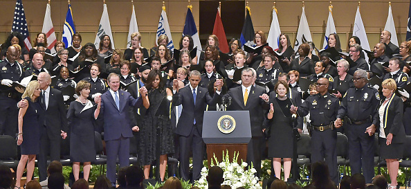 "Dignitaries join hands on stage during the singing of ""The Battle Hymn of the Republic"" during an interfaith memorial service for the victims of the Dallas police shooting at the Morton H. Meyerson Symphony Center on July 12, 2016 in Dallas, Texas.President Barack Obama attended a somber memorial Tuesday to five police officers slain in a sniper ambush in Dallas, as he seeks to unify a country divided by race and politics. / AFP / MANDEL NGAN (Photo credit should read MANDEL NGAN/AFP/Getty Images)"