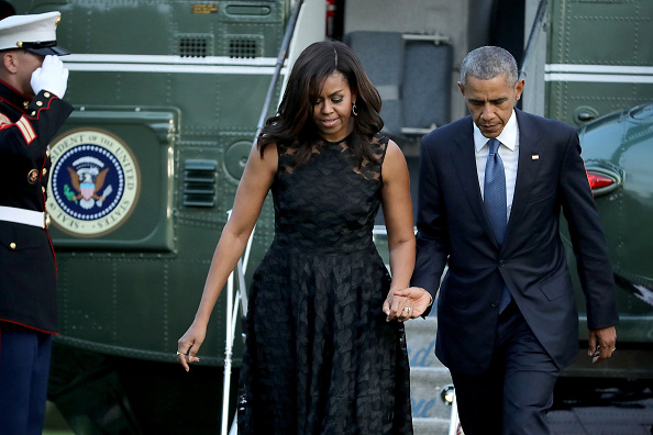 WASHINGTON, DC - JULY 12: (AFP OUT) U.S. President Barack Obama (R) and first lady Michelle Obama walk across the South Lawn after returning to the White House on Marine One July 12, 2016 in Washington, DC. The Obamas were returning from Dallas where they attended a public memorial service for the five Dallas police officers who were killed by a sniper last week during a Black Lives Matter demonstration. (Photo by Chip Somodevilla/Getty Images)