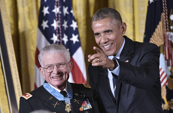 US President Barack Obama points to cameras after presenting the Medal of Honor to retired US Army Lt. Colonel Charles Kettles during a ceremony in the East Room of the White House on July 18, 2016 in Washington, DC. Lt. Colonel Kettles was awarded the Medal of Honor for conspicuous gallantry while serving in Vietnam. / AFP / MANDEL NGAN (Photo credit should read MANDEL NGAN/AFP/Getty Images)