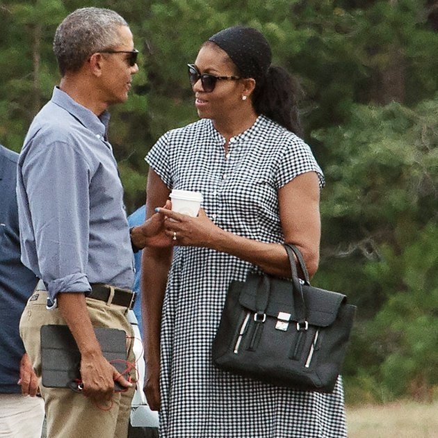 US President Barack Obama and First Lady Michelle Obama chat while waiting for their daughters Malia and Sasha to board Marine One at Martha's Vineyard airport in Edgartown, Massachusetts, on August 21, 2016 as they depart for Washington after a two-week holiday on the island. / AFP / NICHOLAS KAMM (Photo credit should read NICHOLAS KAMM/AFP/Getty Images)