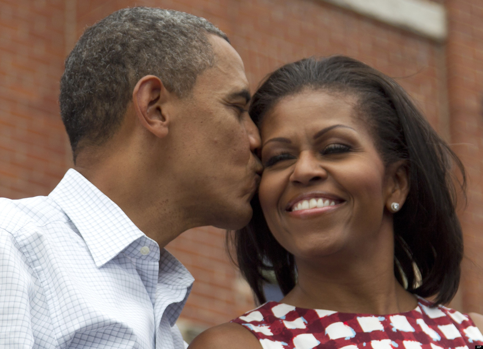 President Barack Obama kisses first lady Michelle Obama on stage at a campaign event at the Alliant Energy Amphitheater, Wednesday, Aug. 15, 2012, in Dubuque, Iowa,  during a three day campaign bus tour through Iowa.  (AP Photo/Carolyn Kaster)